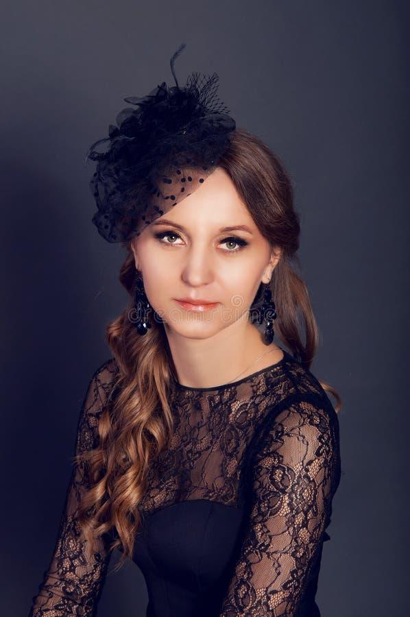 Den eleganta unga kvinnan i svart snör åt klänningen och skyler hatten med långt c arkivfoto