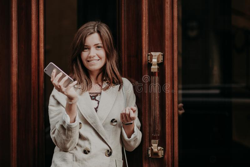 Den eleganta ursnygga damen i regnrocken, hållmobiltelefon, väntar på appell, poserar utomhus- near dörrar som går för arbete, kä arkivbilder