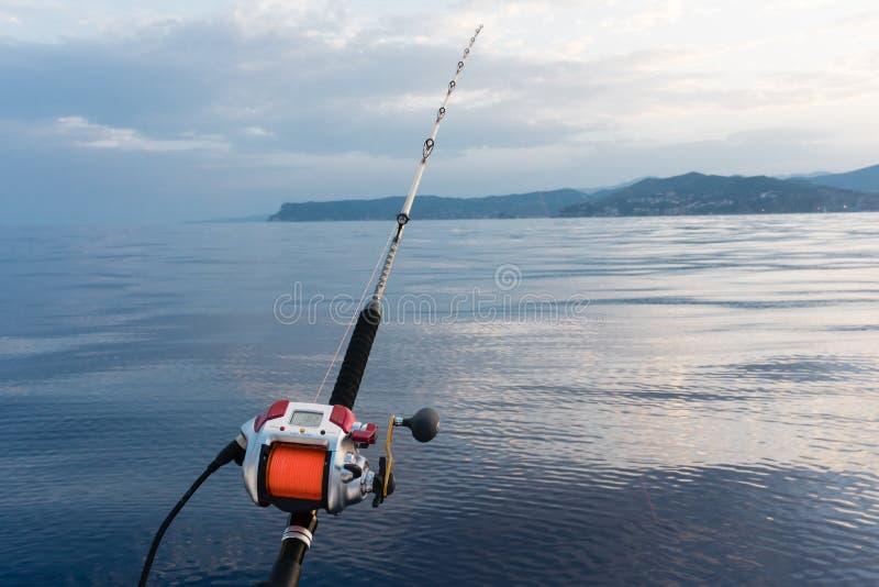 Den elektriska fiskerullen monterade på en stång med havet i backgrounen arkivfoto