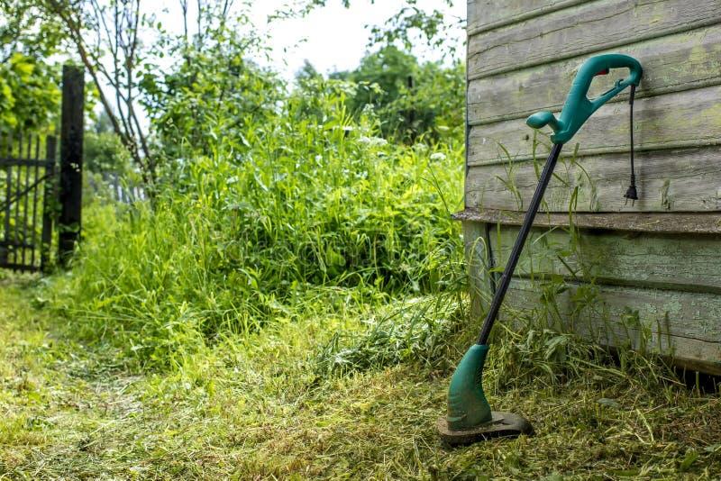 Den elektriska gräsbeskäraren står i trädgården nära huset royaltyfri bild