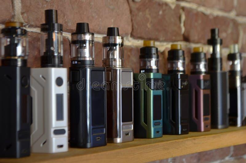 Den elektroniska cigaretten p? en bakgrund av vape shoppar arkivfoto