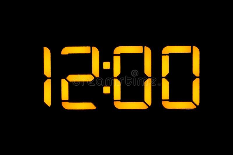 Den elektroniska digitala klockan med gula nummer på en svart bakgrund visar nollnollklockanet för tid tolv av dagen Isolat arkivfoto