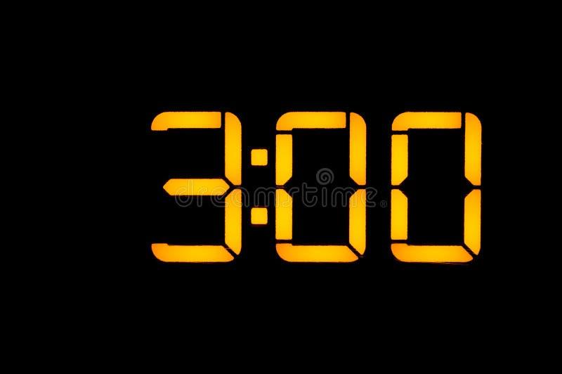 Den elektroniska digitala klockan med gula nummer på en svart bakgrund visar tiden tre noll timmar av natten Isolat n?rbild arkivbild