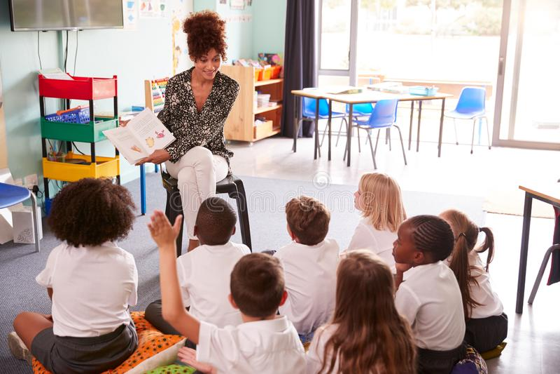 Den elementära eleven som bär enhetliga lönelyfter, räcker för att svara fråga som lärarinnan Reads Book arkivbilder