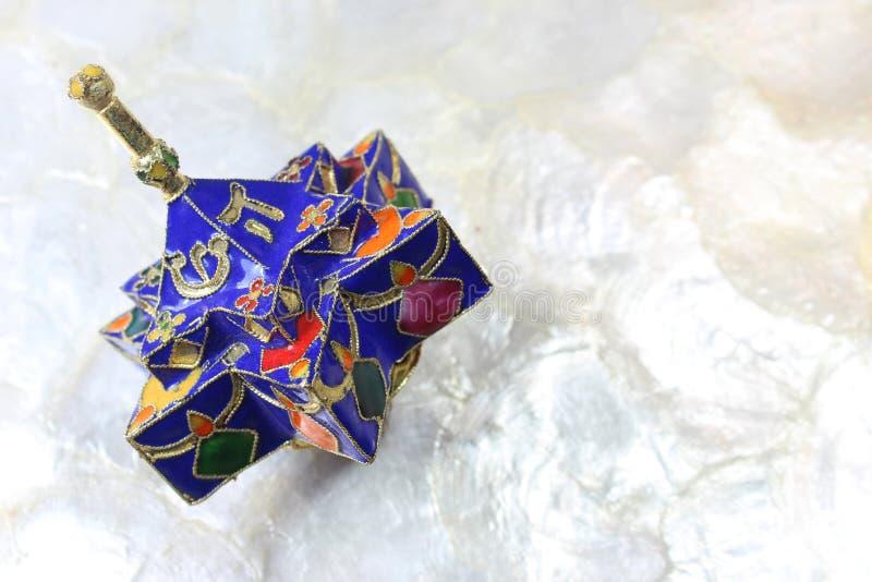 Den emaljerade blåa stjärnan formade Chanukkahdreidel på en mjuk vit bakgrund royaltyfri foto