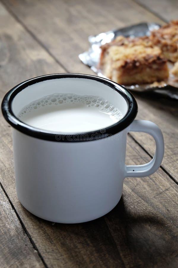 Den emaljerade koppen av mjölkar på en trätabell fotografering för bildbyråer
