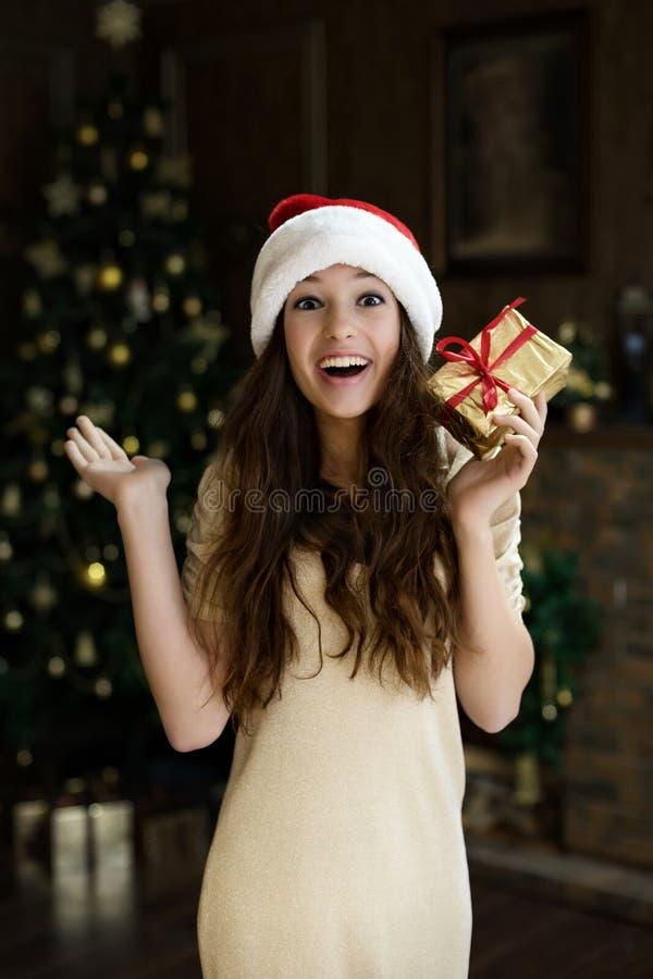 Den emotionella flickan i den santa hatten med entusiasm och glädje och lycka håller fallen för hennes gåva för jul för ` s för d arkivfoto