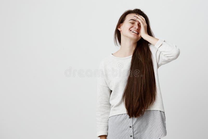 Den emotionella härliga flickan med långt mörkt hår klädde tillfälligt, uppehällehanden på huvudet, leenden joyfully, skratt på v royaltyfria bilder