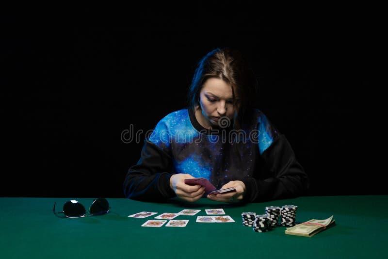 Den emotionella kvinnan i blå kläder och solglasögon är spela kort royaltyfri fotografi