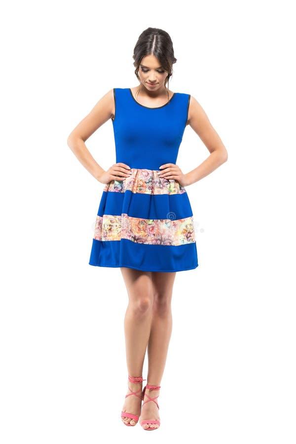 Den emotionella unga kvinnan i den blåa korta klänningen som ner ser med akimbo armar, poserar royaltyfria bilder