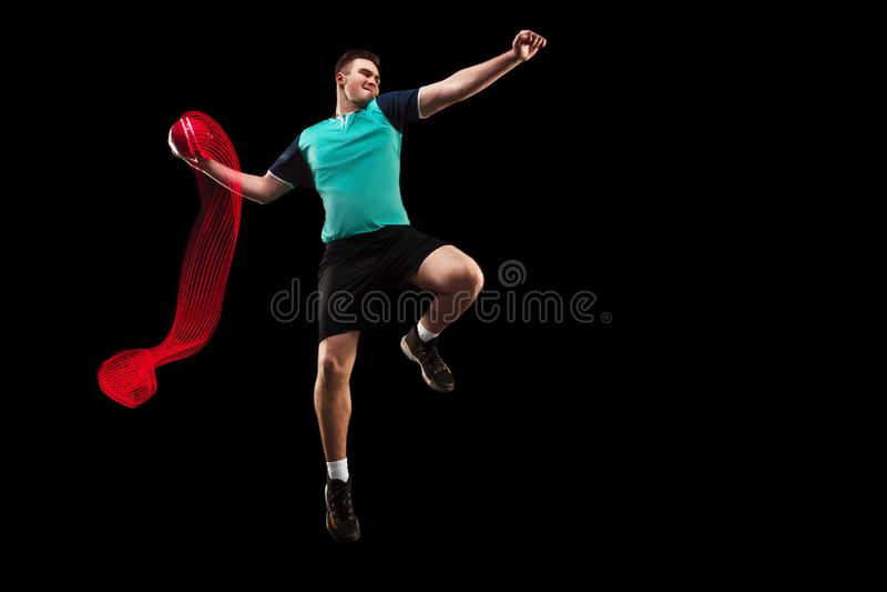 Den en caucasian unga mannen som handbollspelaren på studion på svart bakgrund arkivbild