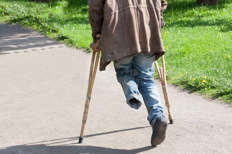 Den enbenta rörelsehindrade personen går parkerar in på kryckor arkivfoto