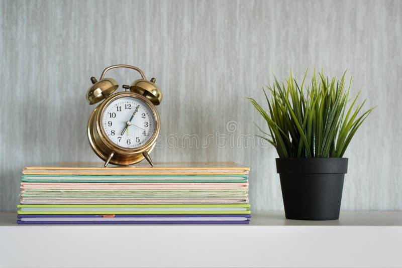 Den encyklopediböcker, växten och ringklockan på den vita hyllan - få organiserad arkivfoto
