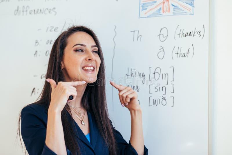 Den engelska kursläraren visar hur man uttalar ljuden arkivbild
