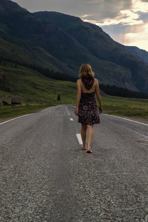 Den enkla barfota kvinnan promenerar bergvägen Lopp, turism och folkbegrepp royaltyfri foto
