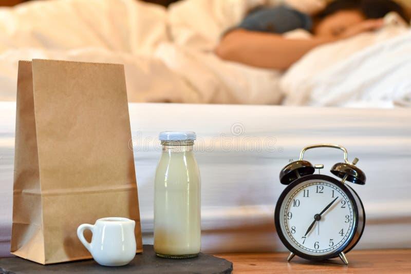 Den enkla frukosten för morgonen med mjölkar, bröd i en pappers- brunt, och ringklockan är beståndsdelen arkivfoton