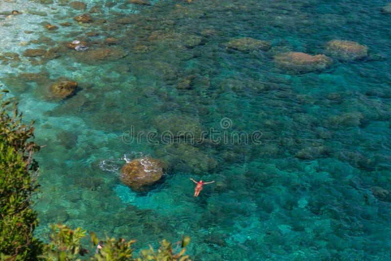 Den enkla kvinnan lägger på det kristallklara vattnet för härlig akvamarin i avkoppling, bästa sikt från höjden arkivbilder