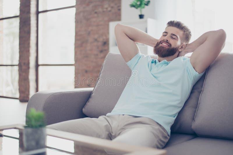 Den enkla lyckliga unga mannen är avslappnande på soffan hemma Han är dren fotografering för bildbyråer