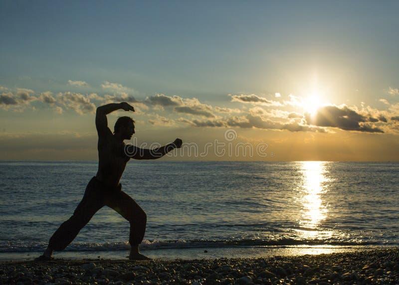 Den enkla mannen gör kampsporter på stranden under solnedgångtid Wushu fotografering för bildbyråer