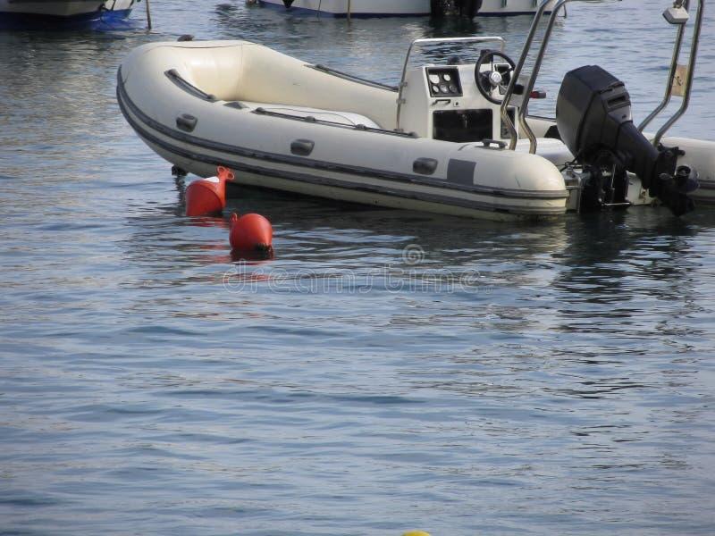 Den enkla uppblåsbara jollen med utombordsmotorn ligger på ankaret i en hamn italy tuscany royaltyfri fotografi