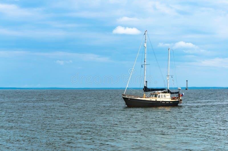 Den enkla yachten med fällt ned seglar, den svartvita yachten på waten arkivbild