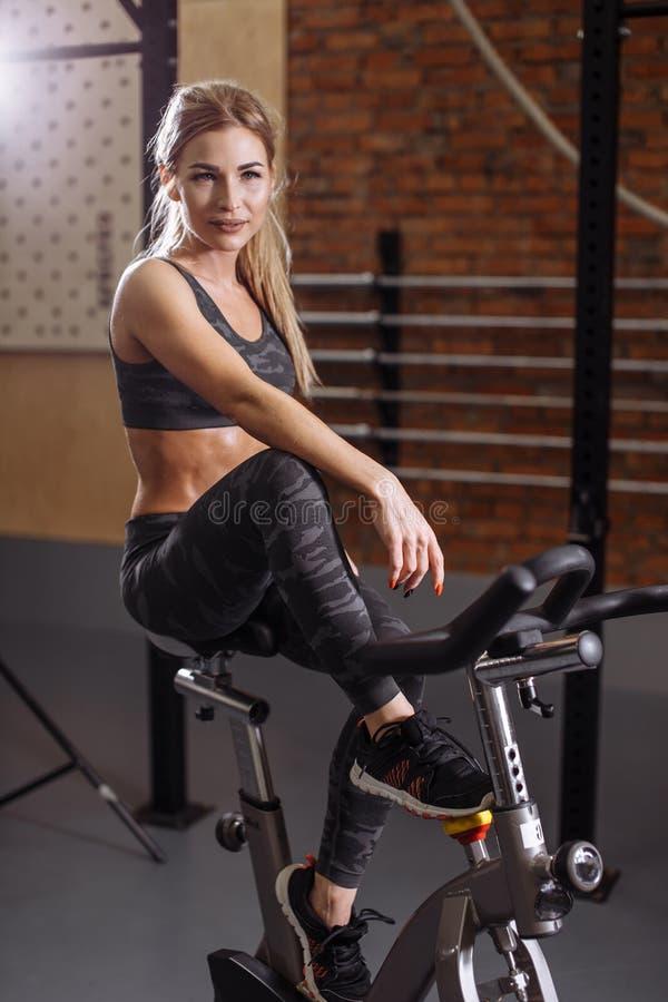 Den enorma blonda kvinnan vilar, når han har utarbetat på den stationära cykeln på idrottshallen arkivfoto