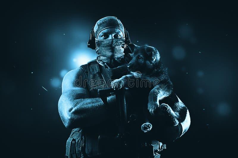 Den enorma militära mannen rymmer en liten valp i hans armar arkivbilder