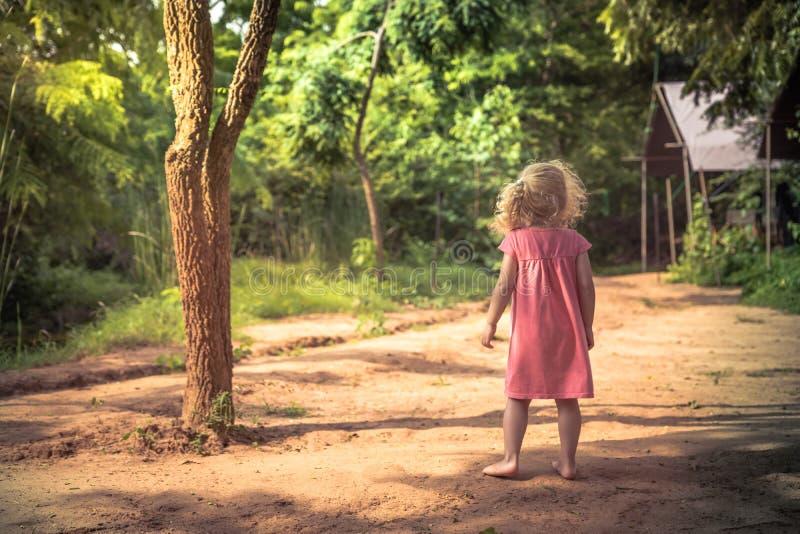 Den ensamma barnflickan som barfota bara står på den lantliga bygdvägen bland träd parkerar in, och ser in i avståndsbegreppschil royaltyfri foto