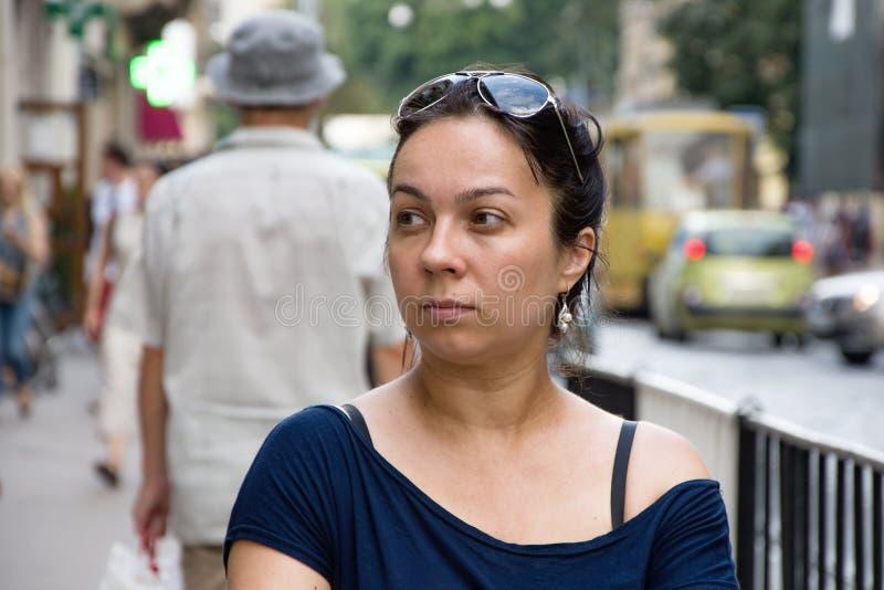 Den ensamma brunetten ser hänsynsfullt och ler in av den europeiska gatan royaltyfri bild