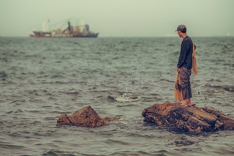 Den ensamma fiskaren stirrar ut på den stora fiskebåten royaltyfria bilder