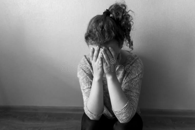 Den ensamma flickan sitter på golvet och gråter täcka hennes framsida med hennes händer, svartvitt foto royaltyfri foto