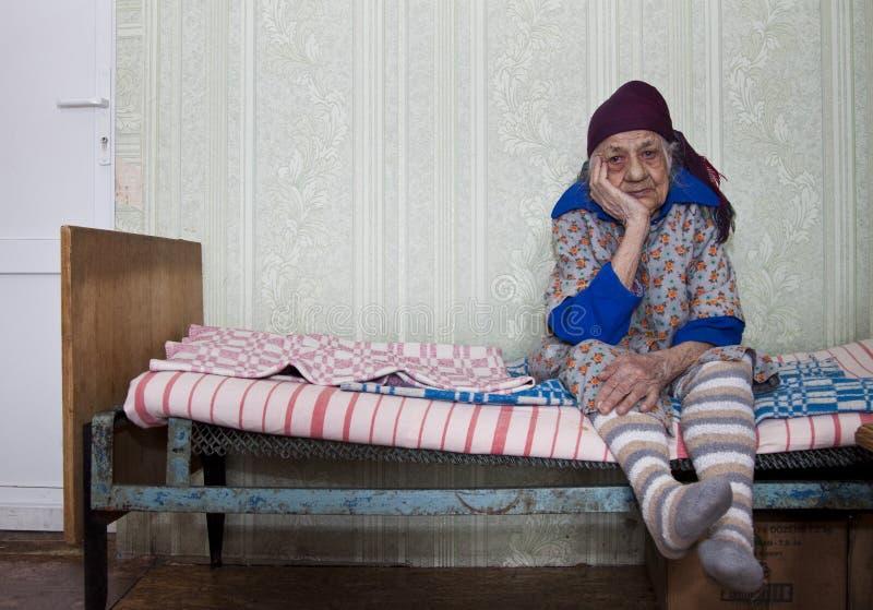 Den ensamma gamla kvinnan är ledsen arkivfoto