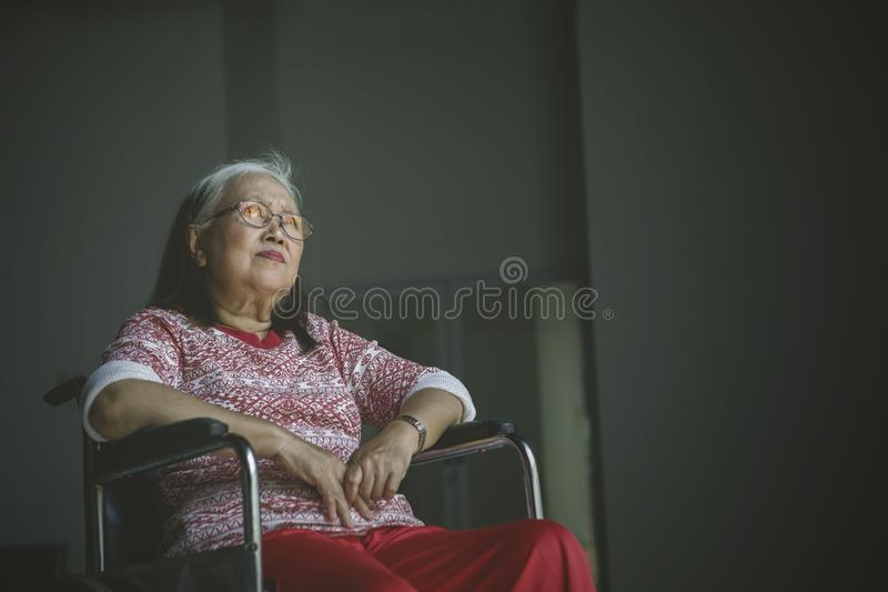 Den ensamma höga kvinnan ser eftertänksam i en rullstol royaltyfria foton