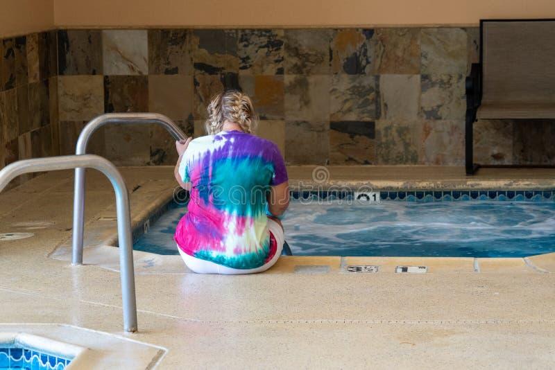 Den ensamma kvinnliga tillbaka sikten sitter med hennes fot som blöter i ett varmt hotell, badar Begrepp för att koppla av, brunn royaltyfri fotografi