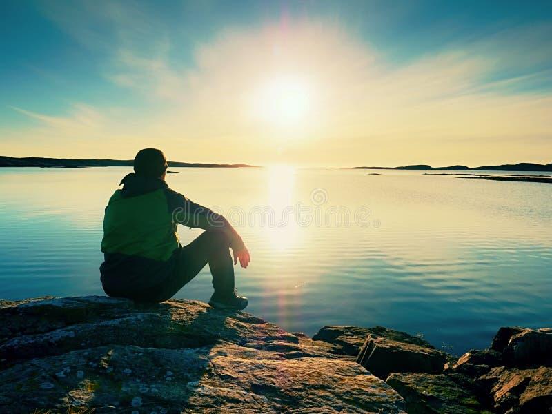 Den ensamma manfotvandraren sitter bara på kust och tycka omsolnedgången Sikt över den steniga klippan till havet royaltyfri fotografi