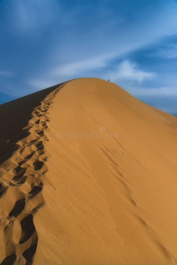 Den ensamma mannen promenerar vapnet av en enorm sanddyn mot den blåa molniga himlen som lämnar bak honom spår på sanden fotspår royaltyfria bilder