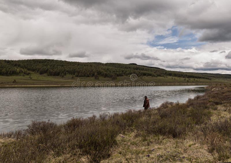 Den ensamma mannen står på kusten av en bergsjö höstsäsong moln över bergen solo fotvandra concepte arkivbild
