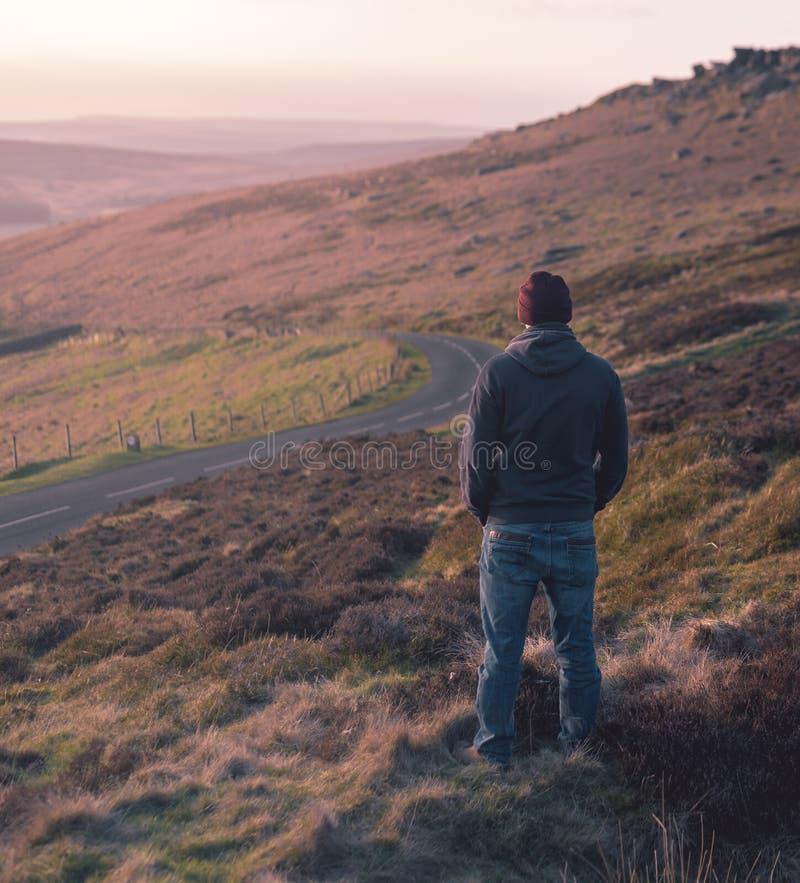Den ensamma mannen stirrar ut över grässlätt under solnedgång royaltyfri foto