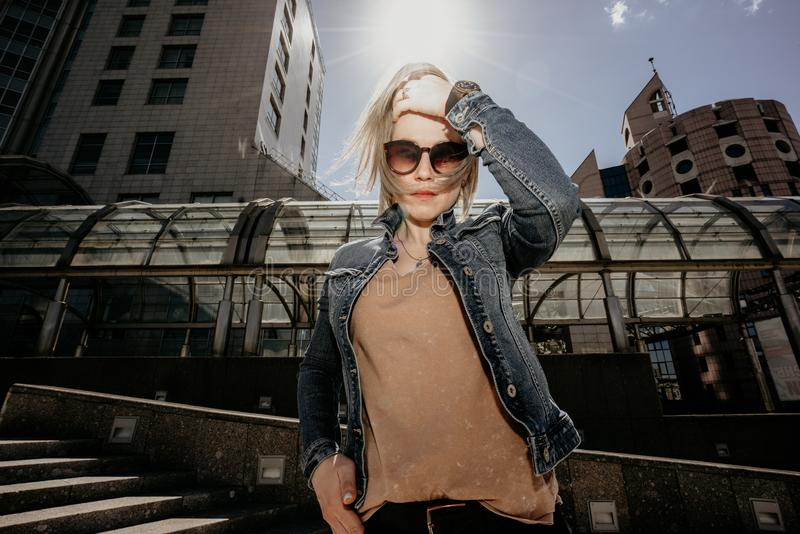 Den ensamma moderna kvinnan rätar ut löst vitt hår Liv i en storstad arkivfoto