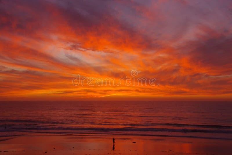 Den ensamma personen på stranden vänder mot en härlig solnedgång fotografering för bildbyråer