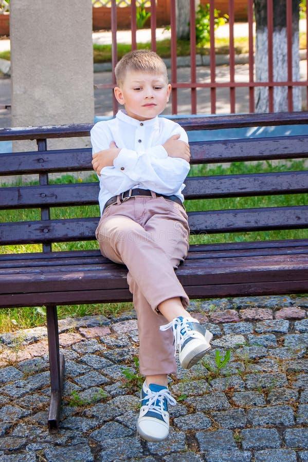 Den ensamma pojken göras modlös som sitter på bänk Den kränkta pojken är a fotografering för bildbyråer