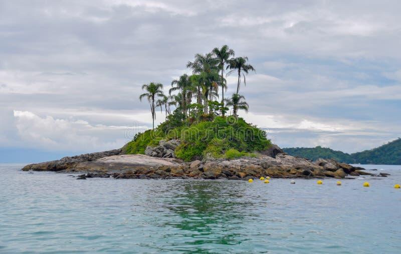 Den ensamma tropiska ön i havet med vaggar och gömma i handflatan arkivfoto