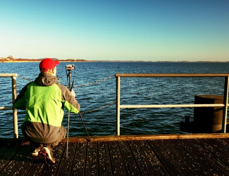 Den ensamma turisten tar foto med kameran och tripoden på träpir royaltyfria bilder