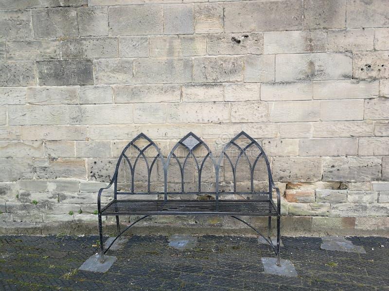 Den ensliga bänken mot gammalt stenar väggen royaltyfri bild