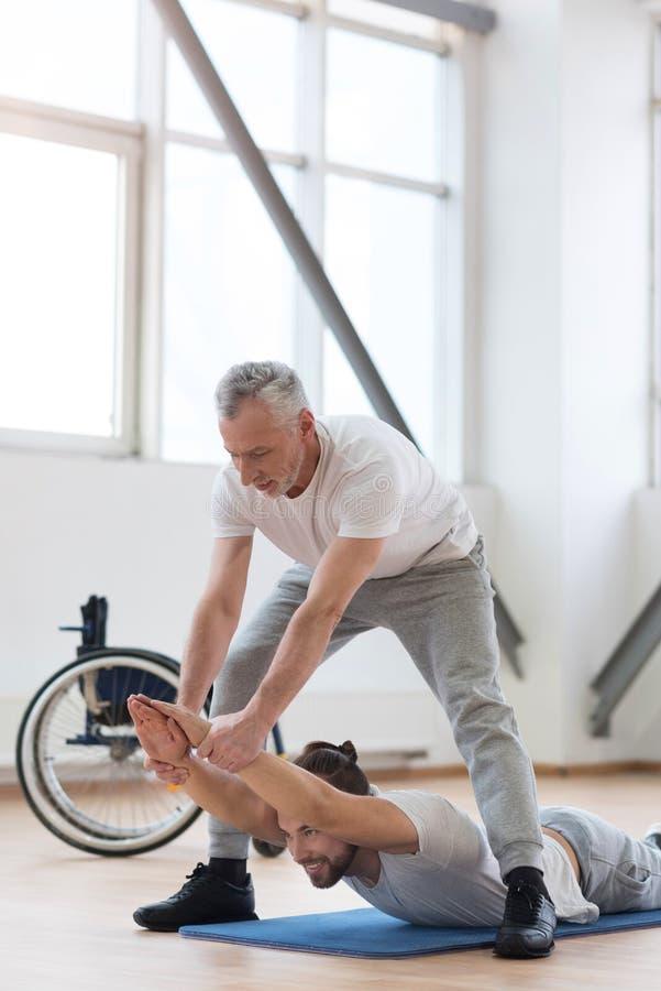 Den erfarna fysiska terapeuten som utarbetar med, inaktiverade i idrottshallen arkivbilder