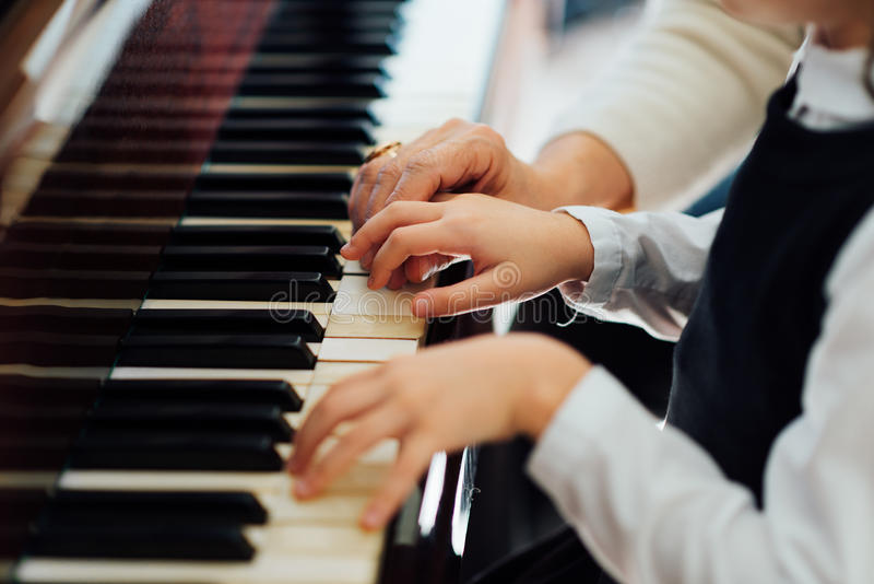 Den erfarna ledar- pianohanden hjälper studenten royaltyfria foton