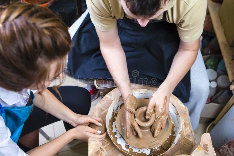 Den erfarna manliga keramikern handleder Working med den kvinnliga lärlingen med Clay Lump på keramikerns hjul i seminarium arkivfoton