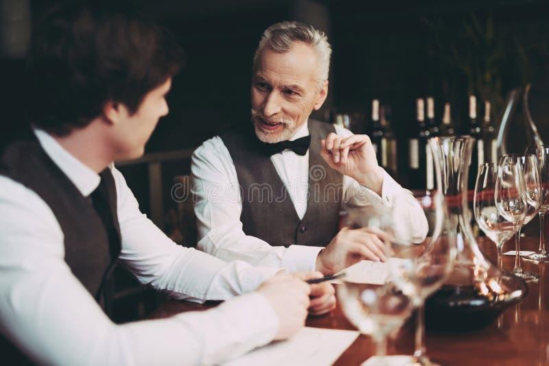 Den erfarna sommelieren gör anmärkningar om smakkvaliteter av vin att dricka sammanträde i restaurang royaltyfri foto