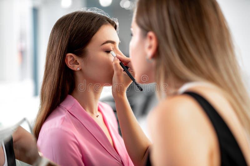 Den erfor makeupkonstnären använder skuggaborsten arkivbilder
