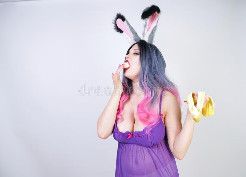 Den erotiska caucasian knubbiga flickan i en genomskinlig damunderkl?derbabydollkl?nning med kanin?ron tycker om bananen och fl?r arkivbild